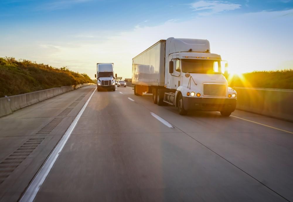 semi trucks driving down a highway